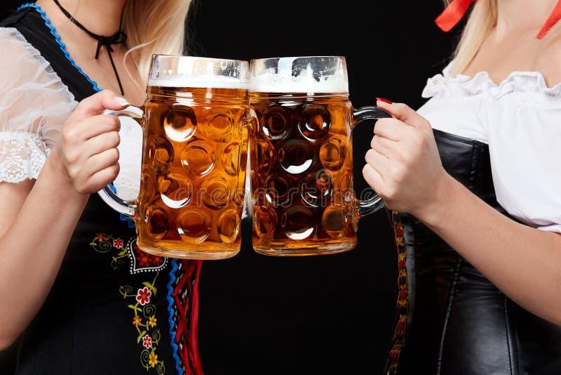 有两个啤酒杯的年轻和美丽的巴法力亚女孩在黑背景 免版税库存图片