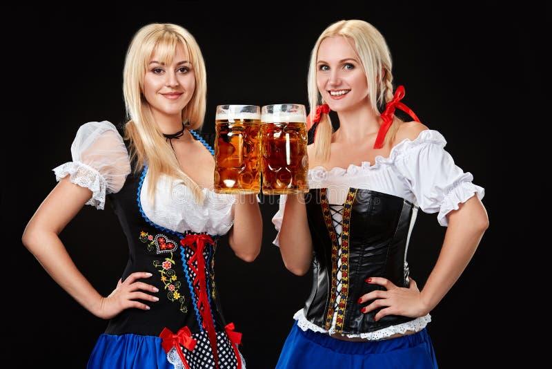 有两个啤酒杯的年轻和美丽的巴法力亚女孩在黑背景 免版税库存照片