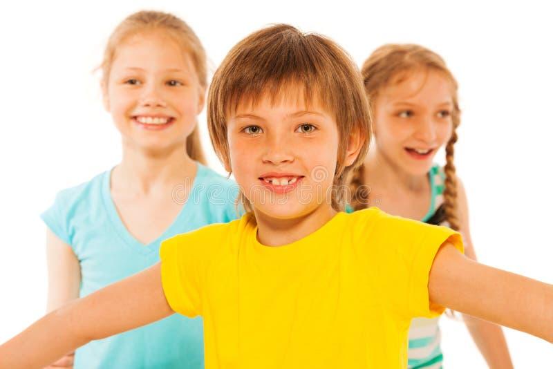 有两个女孩的愉快的微笑的男孩 库存照片