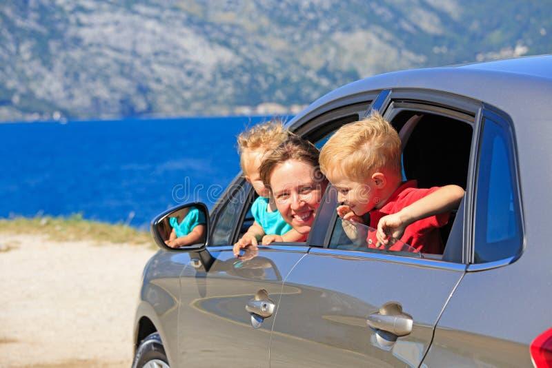 有两个孩子旅行的母亲乘汽车 免版税图库摄影