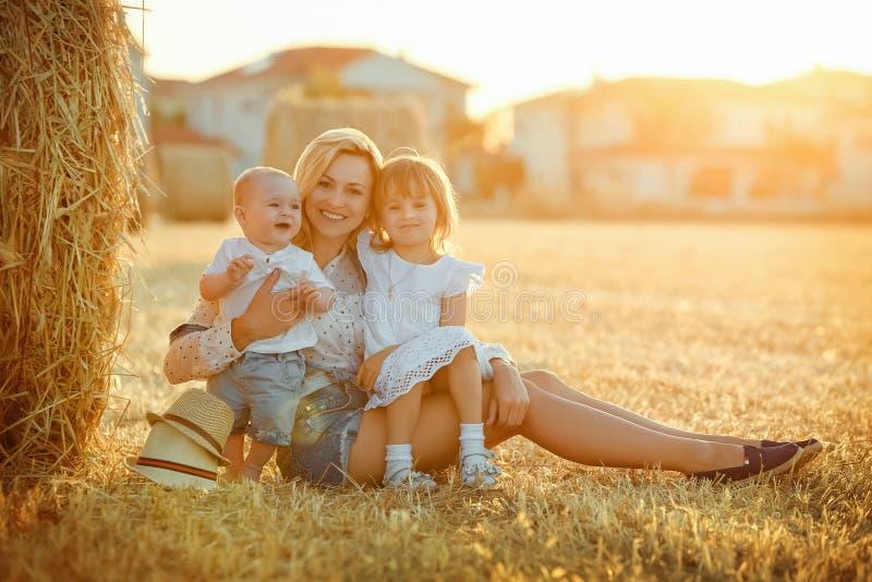 有两个孩子的一个年轻母亲-一个小男婴和女孩 免版税库存照片