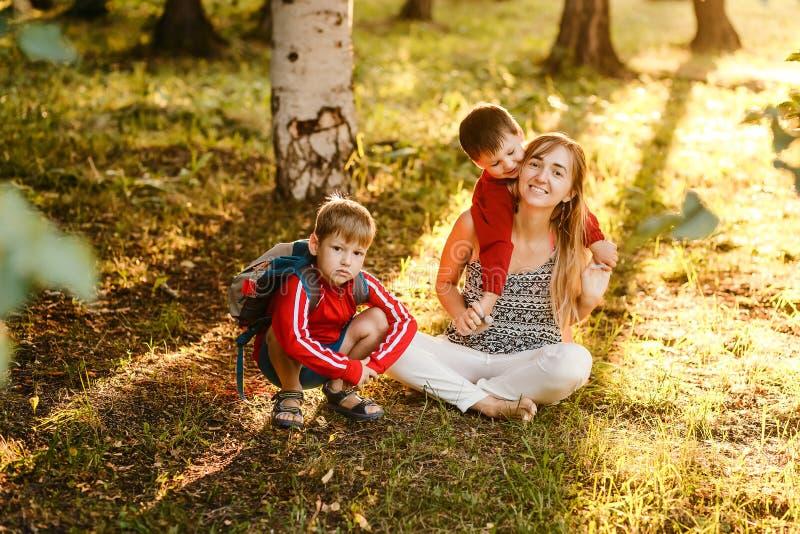 有两个孩子的年轻母亲坐晴朗的草坪 愉快的家庭暑假在公园 库存图片