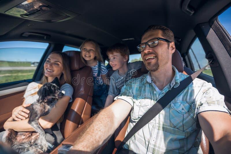 有两个孩子的快乐的家庭去汽车 免版税库存照片