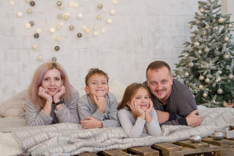 有两个孩子的愉快的家庭在圣诞树说谎下 免版税库存图片