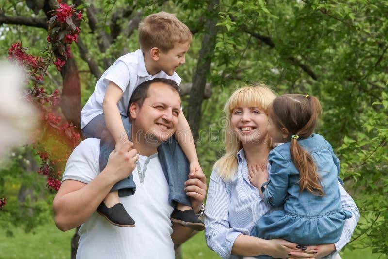 有两个孩子的愉快的家庭在春天庭院里 图库摄影
