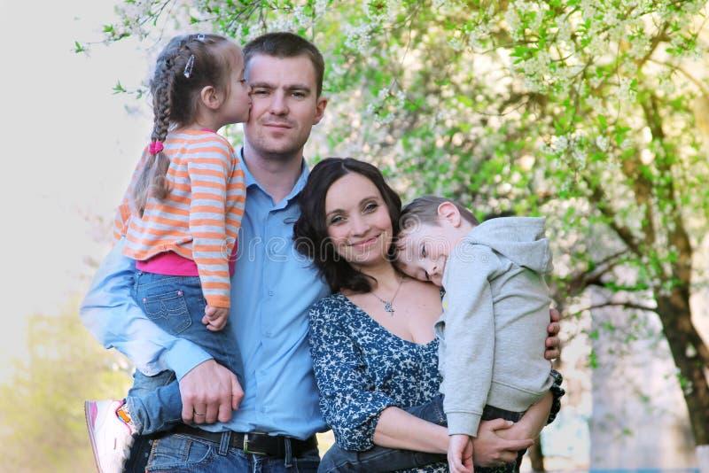 有两个孩子的愉快的家庭在春天树下 库存照片