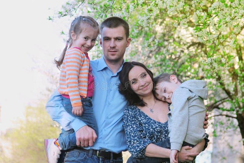 有两个孩子的愉快的家庭在春天 库存照片