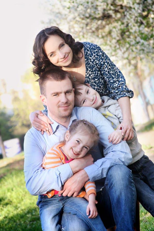 有两个孩子的愉快的家庭在春天 免版税图库摄影