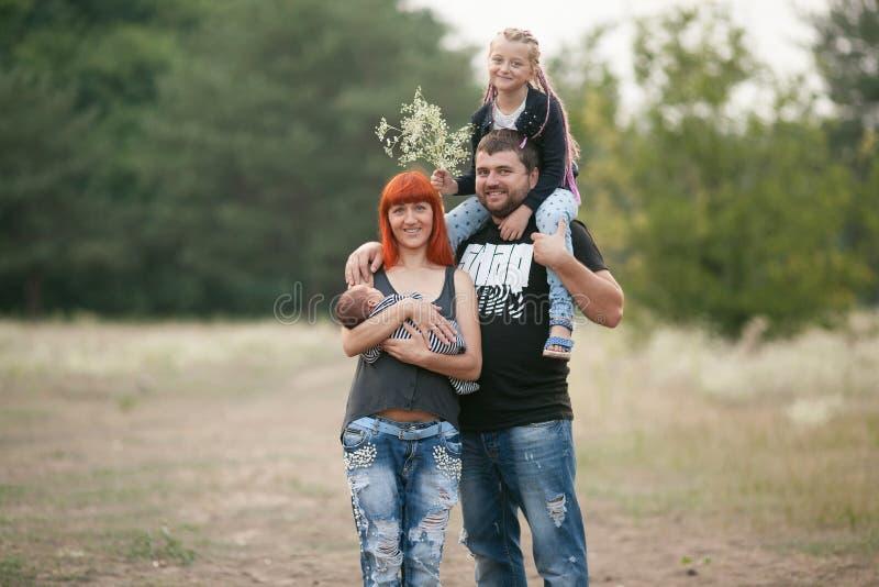 有两个孩子的愉快的年轻家庭步行的在公园 免版税图库摄影
