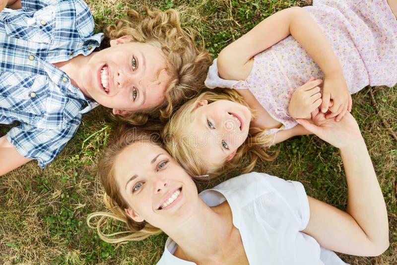 有两个孩子的愉快的母亲在公园 库存图片