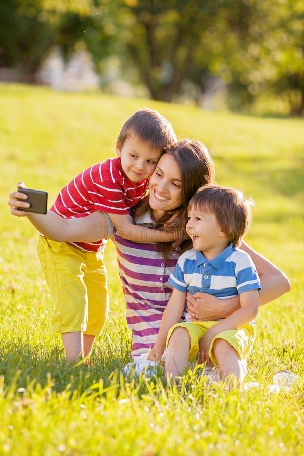 有两个孩子的愉快的母亲,拍照片在公园 免版税库存图片