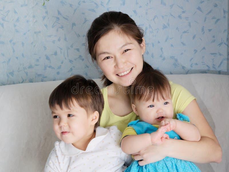 有两个小女孩、多民族家庭与亚裔母亲和女儿的愉快的微笑的妇女 免版税库存照片