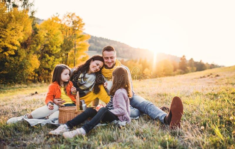 有两个小孩子的一个年轻家庭有野餐在秋天自然在日落 免版税库存照片
