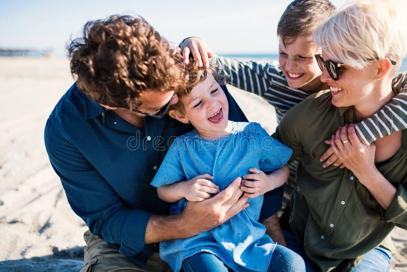 有两个小孩子的年轻家庭户外坐海滩,获得乐趣 库存图片