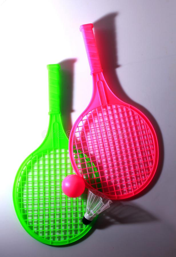 有两个球的绿色和桃红色玩具球拍 库存照片