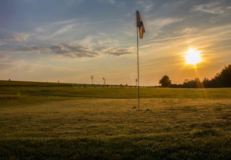 有两个球的高尔夫球场临近在日出的旗子 免版税库存照片