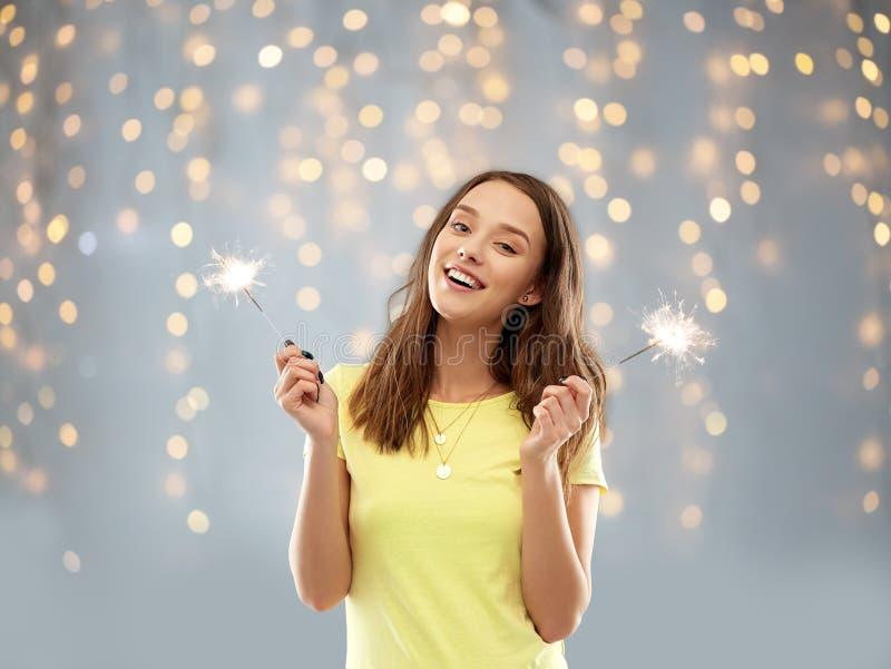 有两个闪烁发光物的愉快的十几岁的女孩在光 免版税库存图片