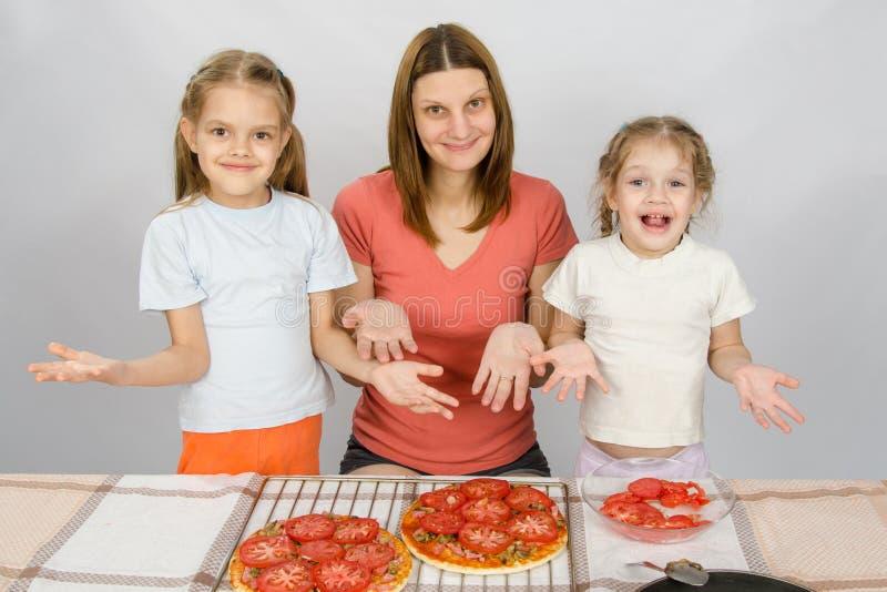有两个年轻女儿的妈妈愉快地显示做的薄饼 图库摄影