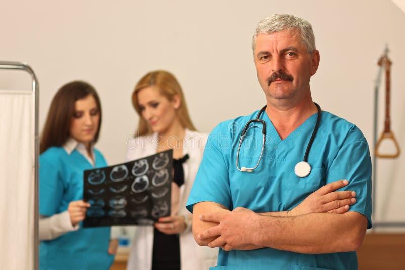 有两位女性护士的成熟男性医生 库存照片