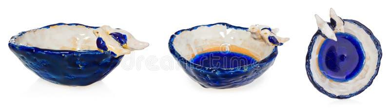 有两只鸟的手工制造陶瓷碗在盘边缘的爱 在颜色蓝色,藏青色,白色,黄色,奶油的杯子 免版税库存照片