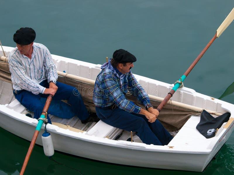 有两名划船者的老木小船贝尔梅奥港的  免版税库存图片