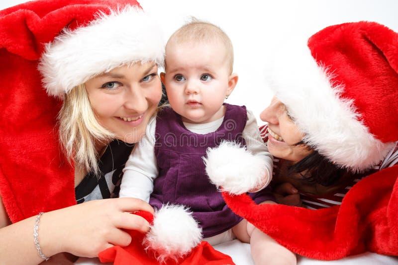 有两名妇女的微笑的婴儿婴孩有圣诞老人帽子的 库存照片
