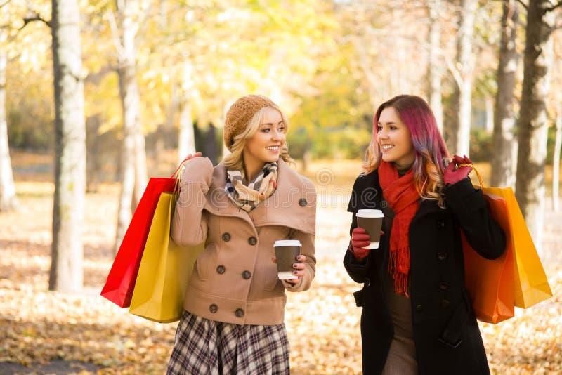 有两名美丽的妇女一次松弛交谈用咖啡 免版税库存图片