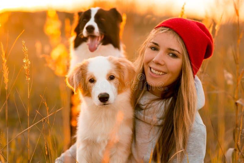 有两在绿色领域放置的凉快的博德牧羊犬狗小狗的微笑女孩 在背景的天空日落 免版税库存照片