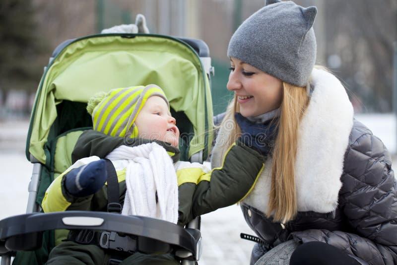 有两岁的儿子的母亲在冬天公园 免版税图库摄影