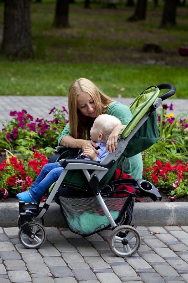 有两岁的儿子的母亲在夏天公园 免版税库存照片
