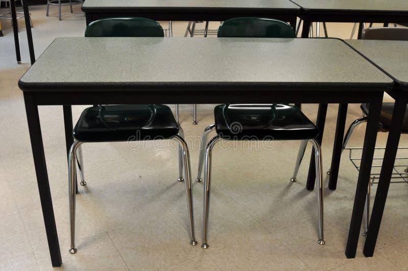 有两把空的椅子的一张学校书桌 免版税库存照片
