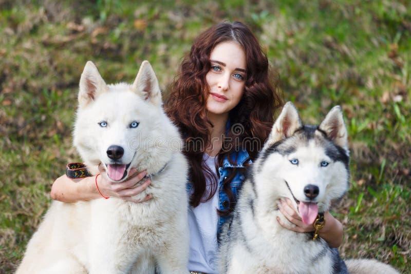 有两条多壳的狗的逗人喜爱的女孩 免版税库存照片