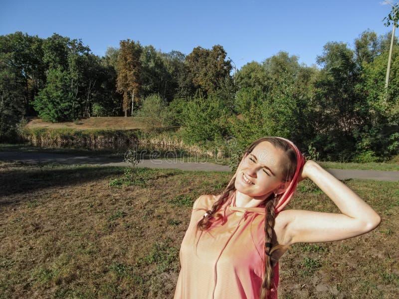 有两条猪尾和闭合的眼睛的愉快的女孩享受晴朗的天气的在公园 年轻俏丽的妇女构筑了她的面孔下 库存照片