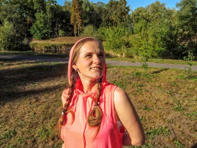 有两条猪尾的年轻成人女孩梦想看对天空,微笑 一名年轻愉快的妇女的画象一件桃红色戴头巾运动衫的 免版税库存图片