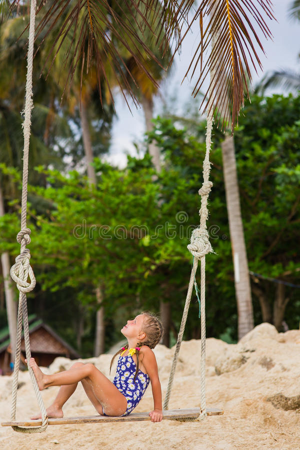 有两条辫子的女孩在摇摆的游泳衣在海滩 免版税库存照片