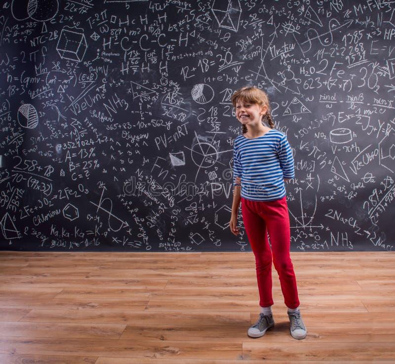 有两条辫子的女孩,有数学符号的大黑板 库存照片