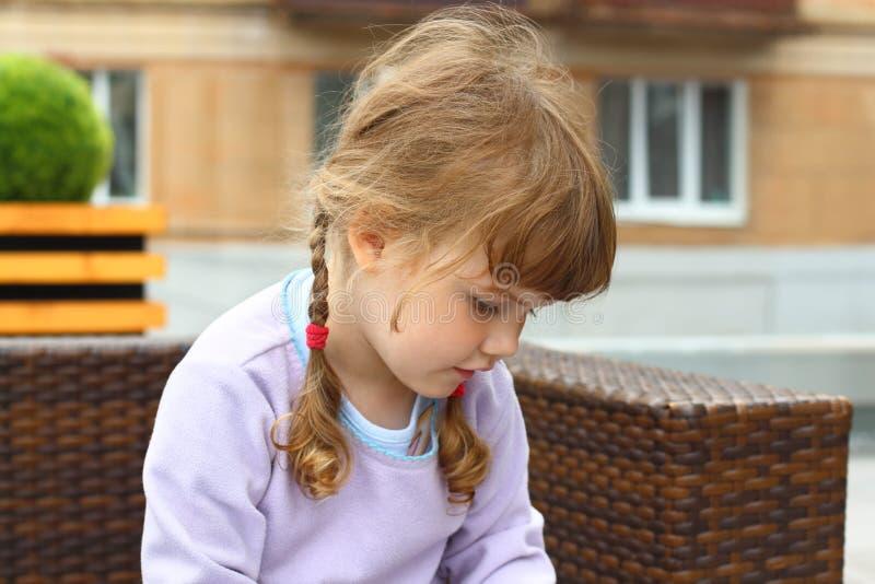 有两条辫子的小女孩坐柳条长沙发 库存照片