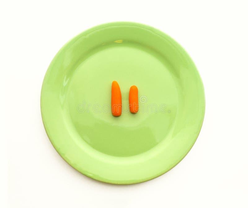 有两棵微小的红萝卜顶视图关闭的绿色板材 免版税库存图片