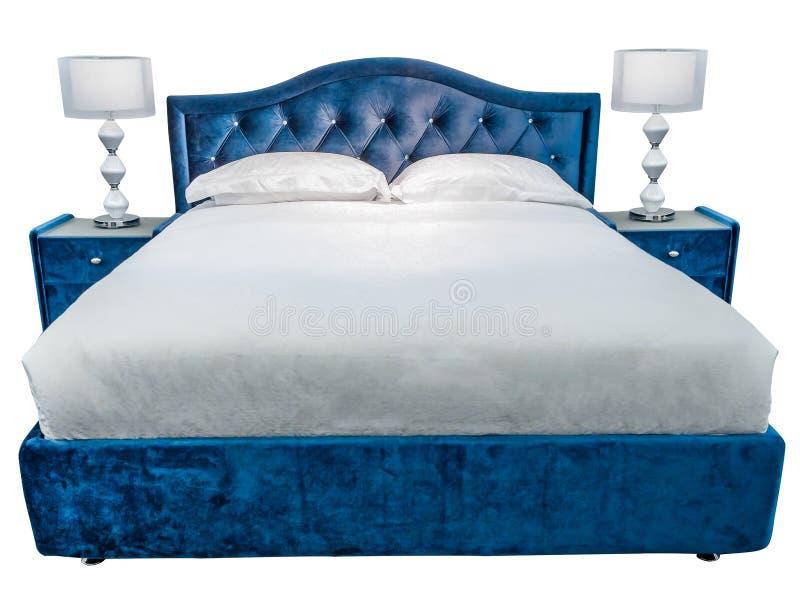 有两盏夜灯的豪华白色蓝色现代床家具在床头柜,与被仿造的盖子,有丝绒的 图库摄影