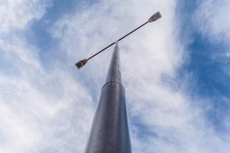 有两盏探照灯的街道路灯柱自反对蓝天背景的白天与白色云彩的 免版税图库摄影
