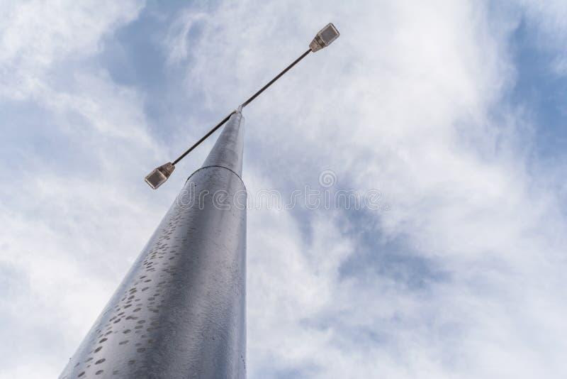 有两盏探照灯的街道路灯柱自反对蓝天背景的白天与白色云彩的 库存照片