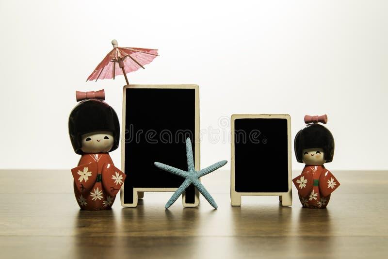 有两空白的黑板的两个日本玩偶与蓝星鱼和红色伞 免版税库存图片