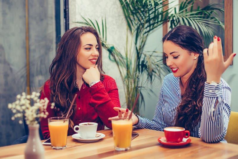 有两美丽的年轻女人坐在咖啡馆,饮用的咖啡和一次宜人的交谈 库存图片