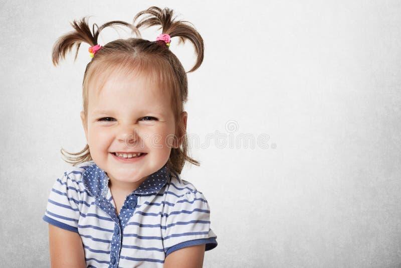 有两马尾的快乐的正面可爱的小孩子,穿戴在镶边T恤杉,表现出宜人的情感,是高兴的 免版税库存照片