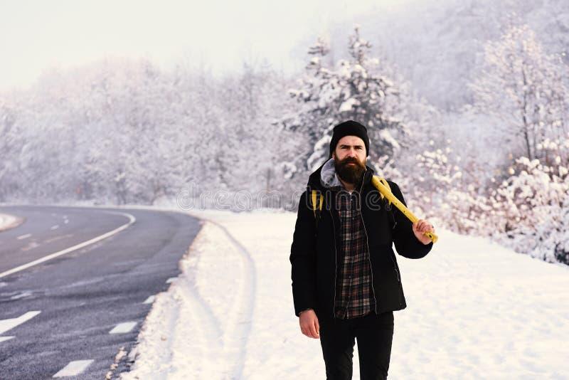 有严密的面孔的在背景的人与雪和路 免版税库存照片