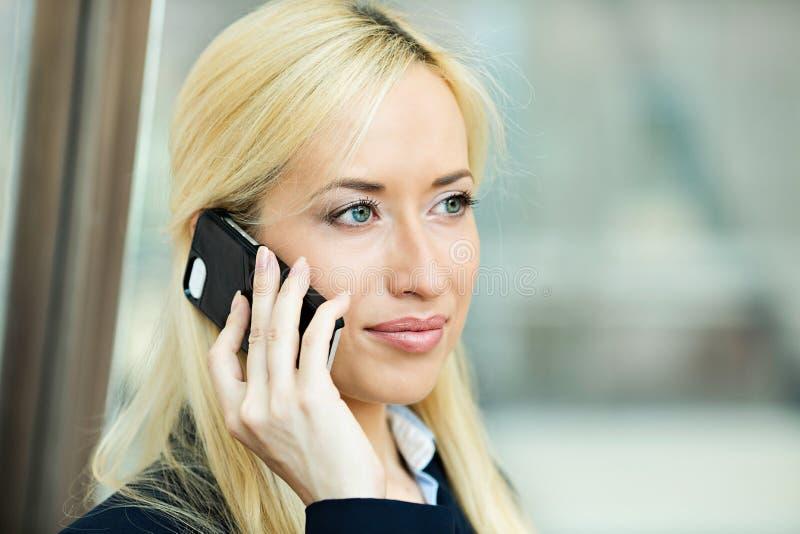 有严肃的女商人在电话的交谈 库存照片