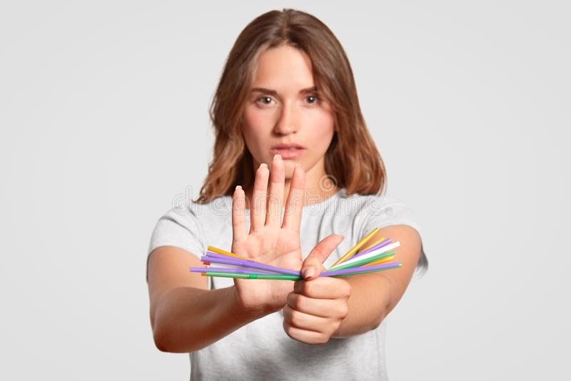 有严肃的表示的欧洲妇女,举行塑料秸杆,对一次性塑料吸管说不倾向于金属, 免版税库存图片