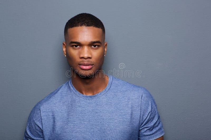 有严肃的表示的英俊的年轻黑人在面孔 图库摄影