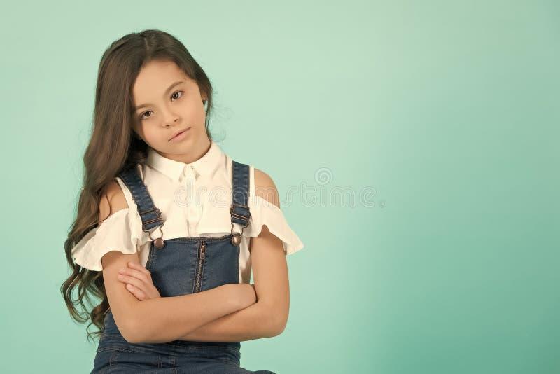有严肃的面孔姿势的女孩用被折叠的手 免版税库存照片