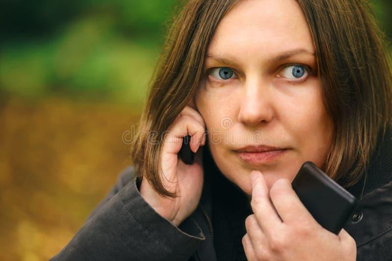 有严肃的面孔表示的妇女谈话在电话在公园 库存照片